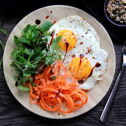 Oeufs sur le plat avec spaghettis de carotte et salade